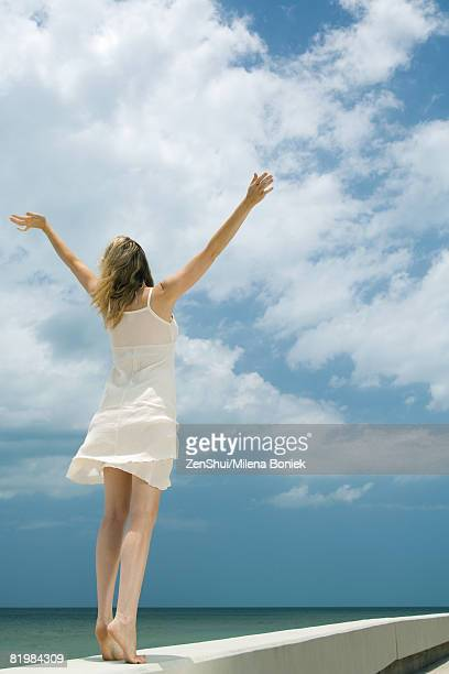Woman in sundress standing next to sea with arms raised, rear view