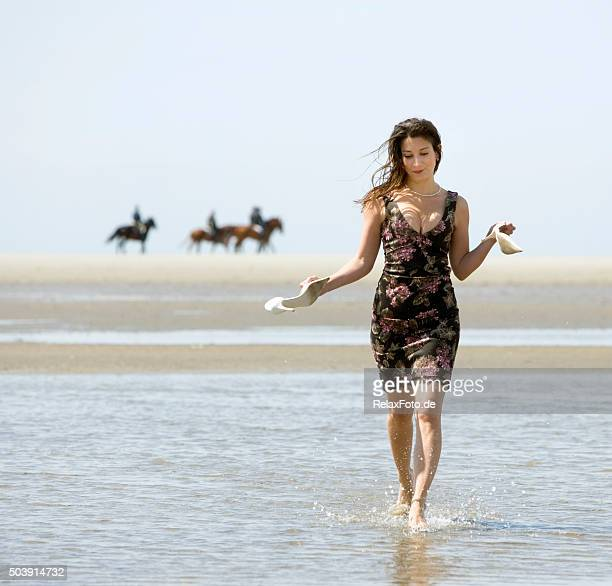 Woman in sundress walking barefooted through tidal pool