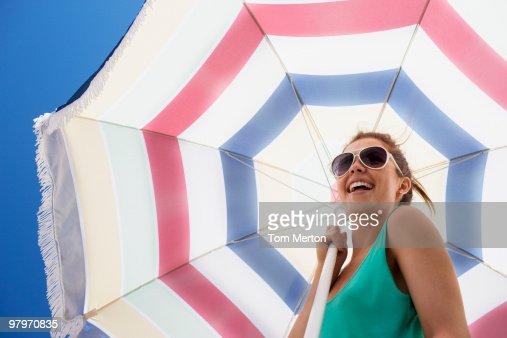 Woman in sunglasses holding beach umbrella