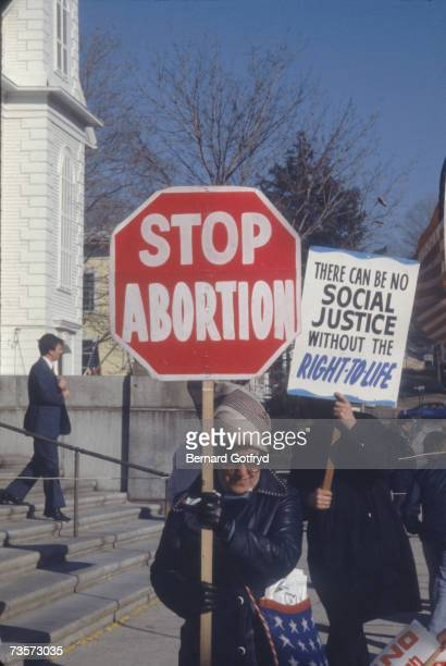 A woman in sunglasses holds up a sign shaped like a stopsign which reads 'Stop Abortion' as she and others protest the procedure outside a building...