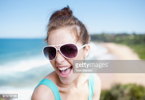 Woman in sunglasses laughing with ocean in background : Stock Photo