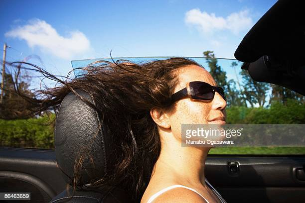 Woman in sunglasses riding in convertible