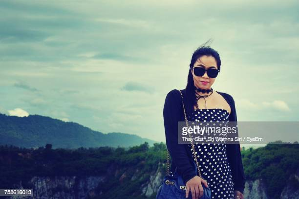 Woman In Sunglasses Standing Against Cloudy Sky