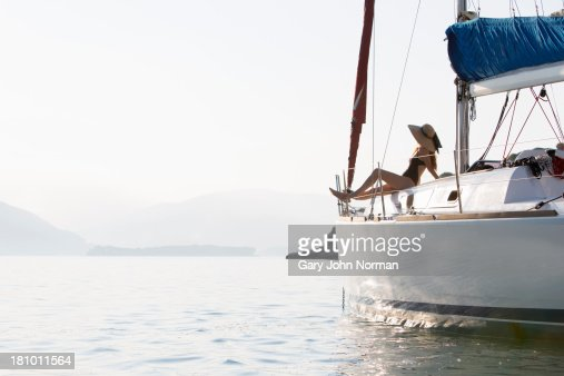 woman in sunhat sits at bow of yacht