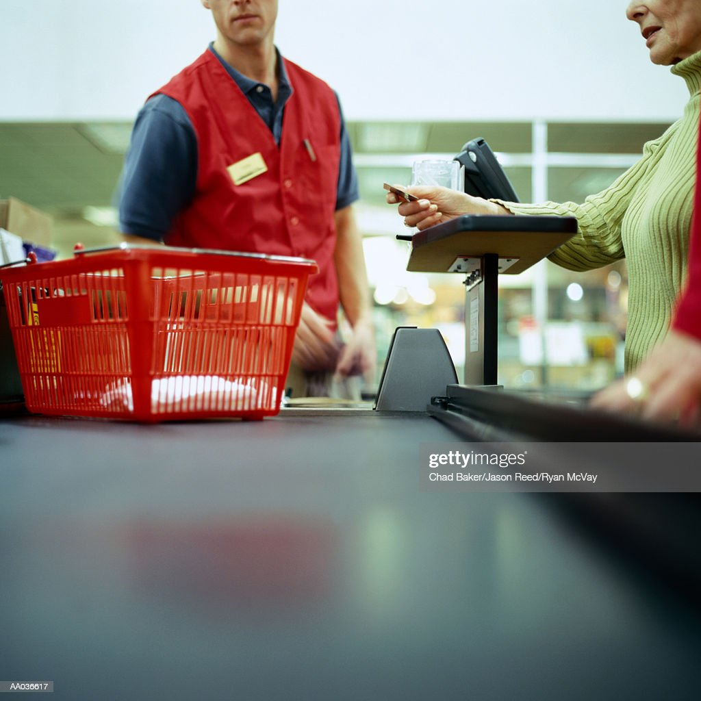 Woman in supermarket using credit card, mid section