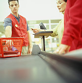 Woman in supermarket using credit card