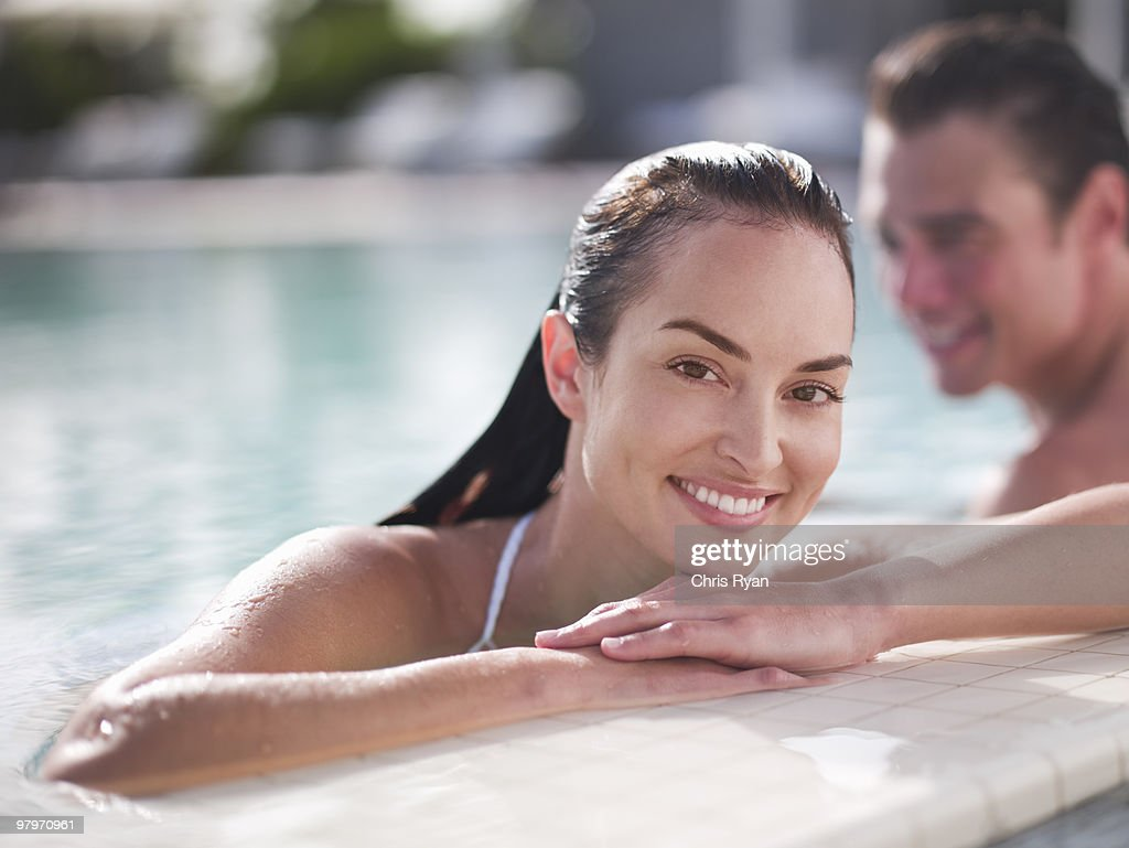 Woman in swimming pool leaning on edge : Stock Photo