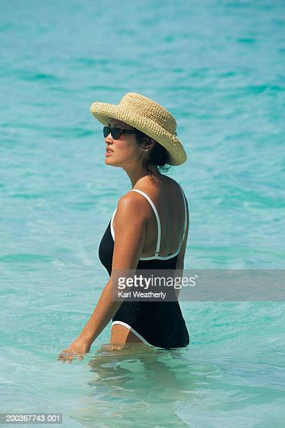 Woman in swimsuit and straw hat wading into sea
