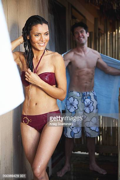 Woman in swimsuit rinsing off in outdoor shower, man smiling