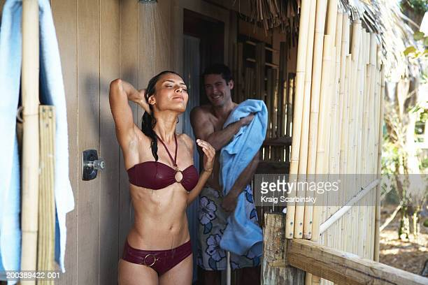 Woman in swimsuit rinsing off in outdoor shower, man toweling dry