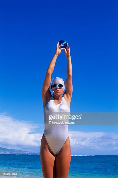 Woman in swimsuit with headset and cd