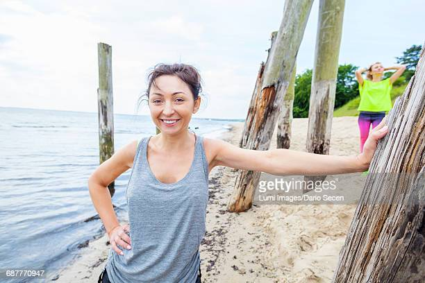 Woman in tank top on beach leaning against wooden post