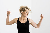 Woman in tank top stretching her arms and smiling