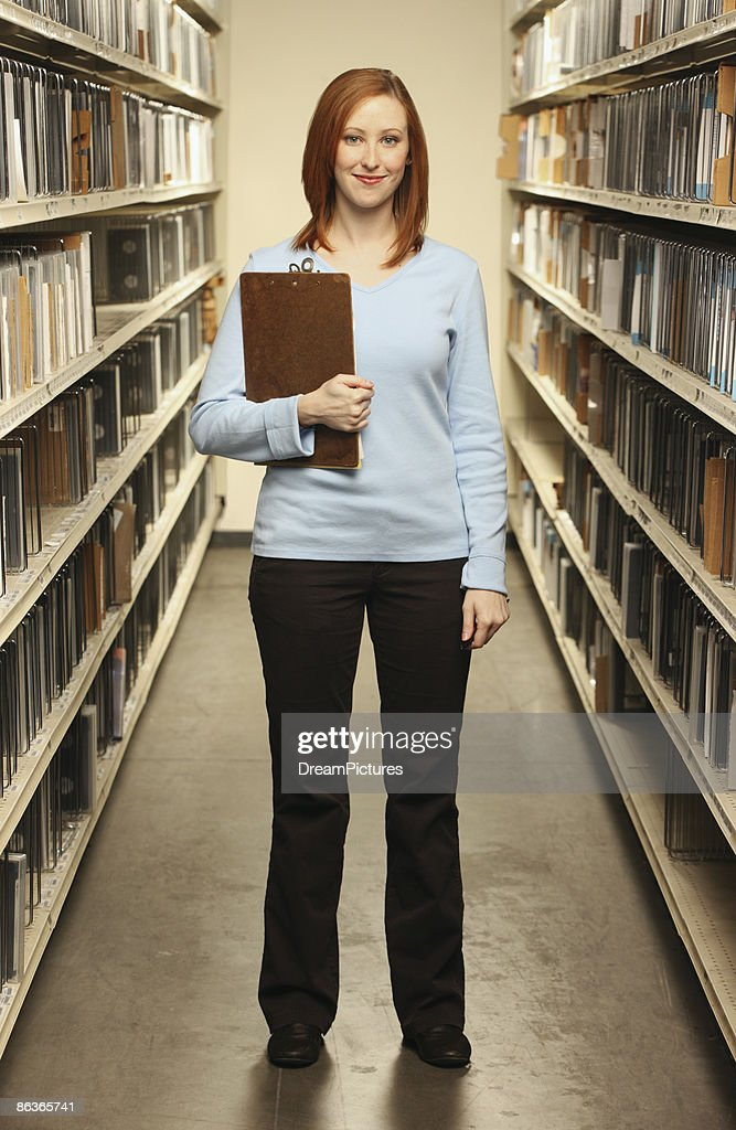 Woman in tape catalogue room.  : Stock Photo