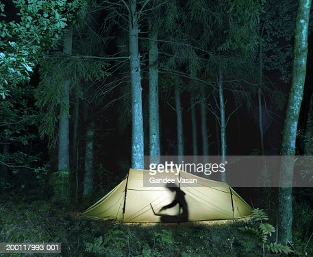 Woman in tent using laptop computer, silhouette : Stockfoto