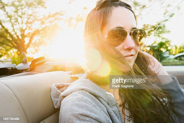 Woman in the Back seat of a Convertible.