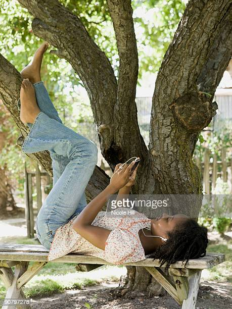 woman in the backyard listening to a digital music player