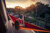 Young woman enjoys sunset relaxing in the hammock on the balcony