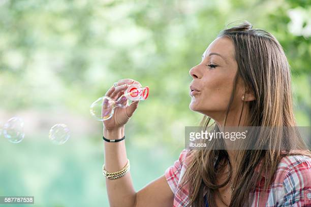 Woman in the park: Blowing bubbles