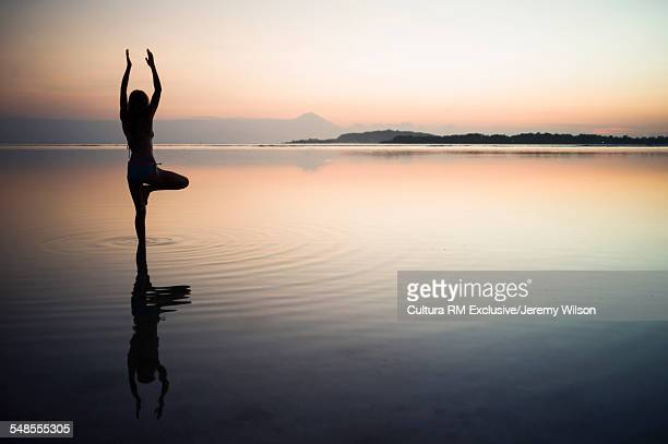 Woman in the sea, in yoga position, rear view, Gili Air, Indonesia