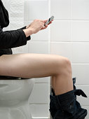 Woman in toilet with a smartphone