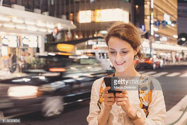 Woman in Tokyo texting at the street