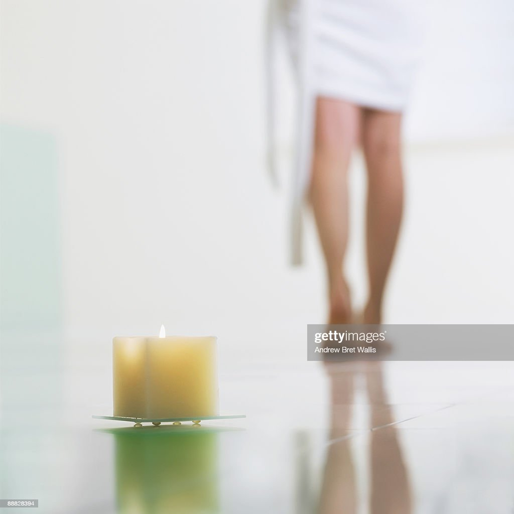 Woman in towel by lit candles