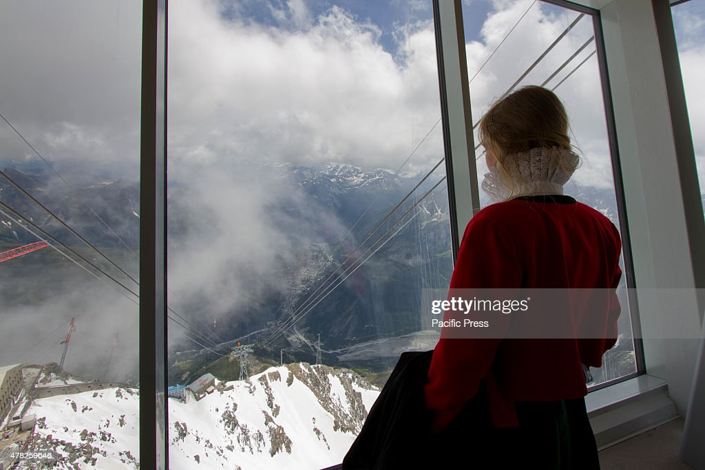 A woman in traditional Aosta Valley costume looks out at the Skyway cable car connecting the city of Courmayeur to Pointe Helbronner in the Mont...