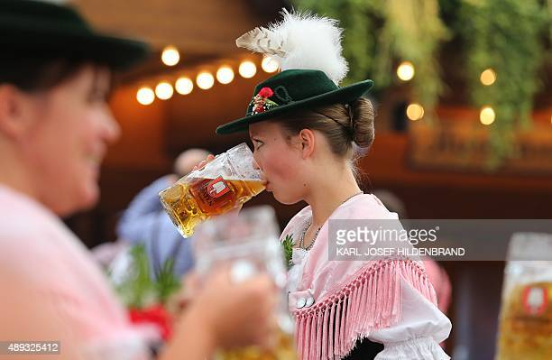 A woman in traditional Bavarian dress drinks a beer in a beer tent at the Theresienwiese fair grounds of the Oktoberfest beer festival in Munich...