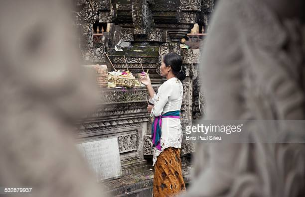 A woman in traditional clothes prays at the Pura Tirta Empul Temple Tampaksiring Bali Indonesia