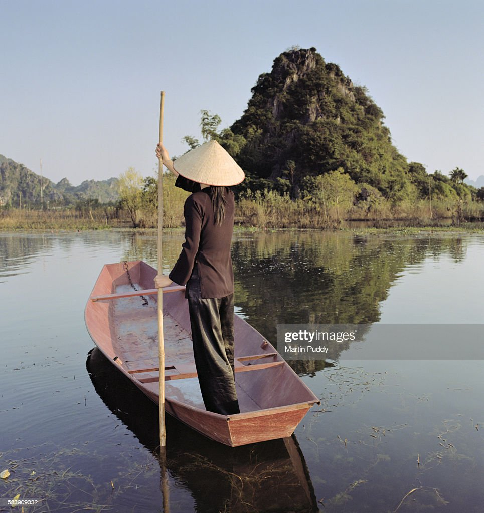 Woman in traditional dress guides a punting boat along river near Perfume Pagoda