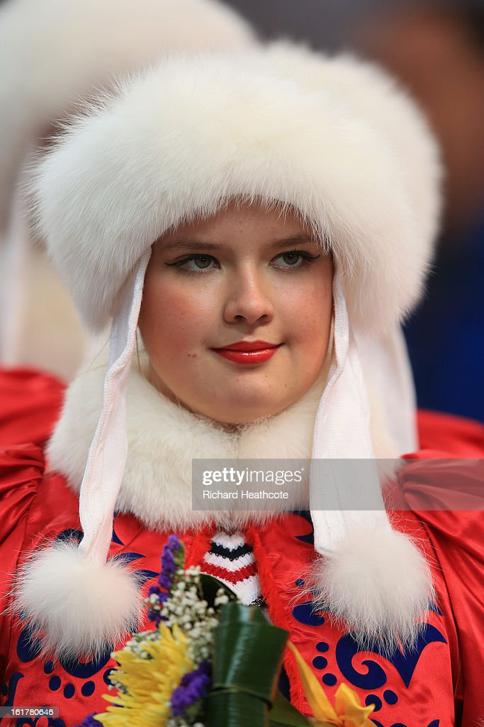 A woman in traditional dress waits to present flowers during the Viessman FIBT Bob & Skeleton World Cup at the Sanki Sliding Center in Krasnya Polyana on February 16, 2013 in Sochi, Russia. Sochi is preparing for the 2014 Winter Olympics with test events across the venues.