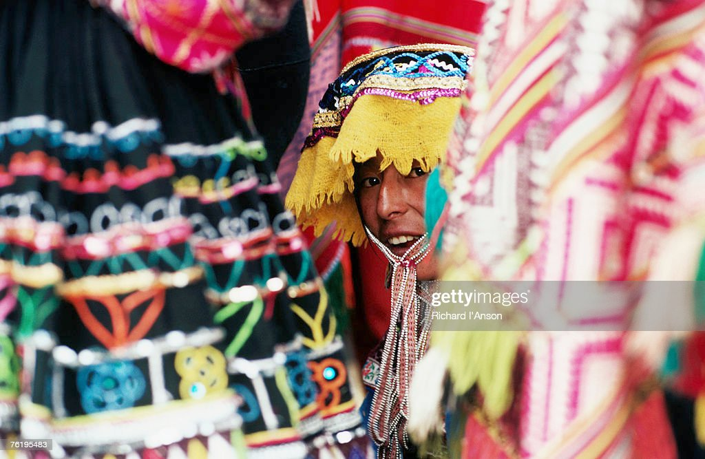 Woman in traditional hat looking through textiles and fabric of stall, Peru, South America : Stock Photo