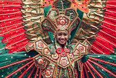 Asian woman in traditional Indonesian costume of Garuda performing ritual dancing ceremony smiling