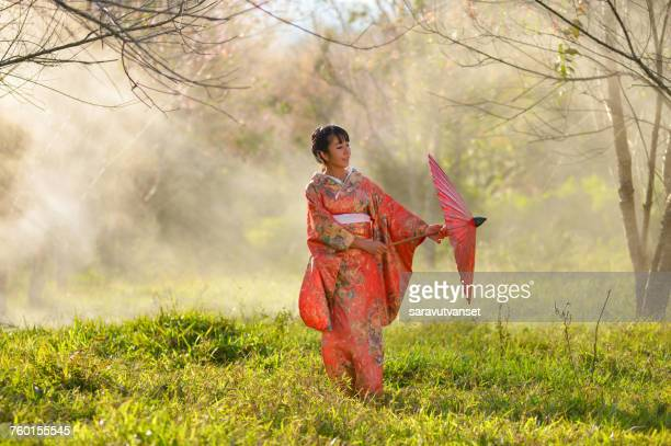 Woman in traditional Japanese clothing in a cherry blossom orchard, Japan
