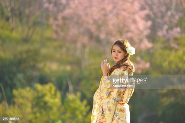Woman in traditional Japanese clothing standing in a cherry blossom orchard, Japan