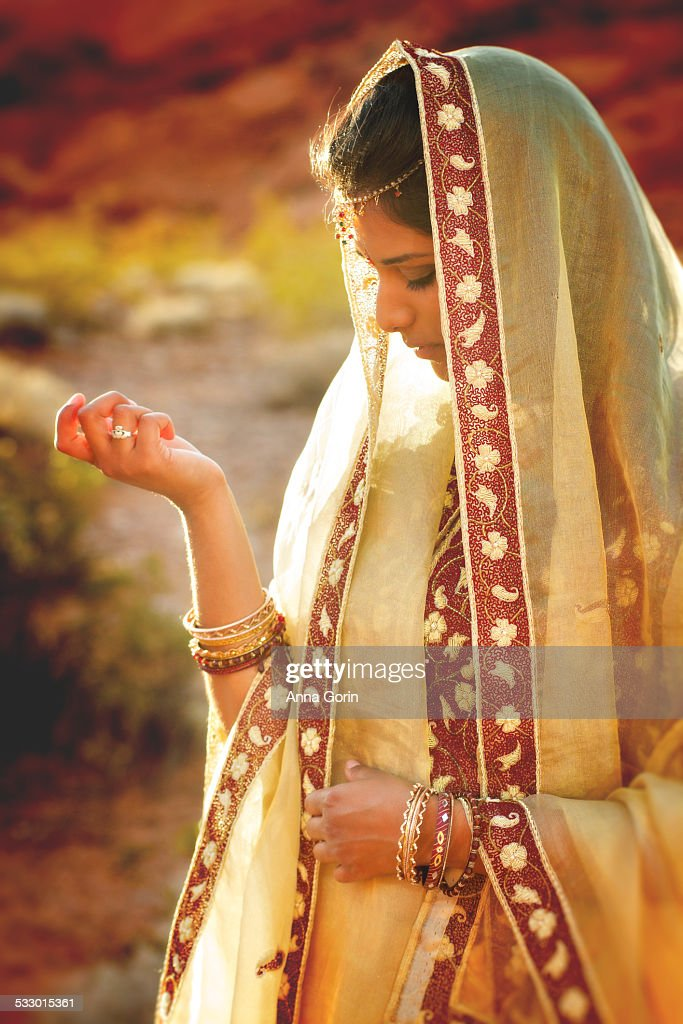 Woman in traditional sari outside at sunset