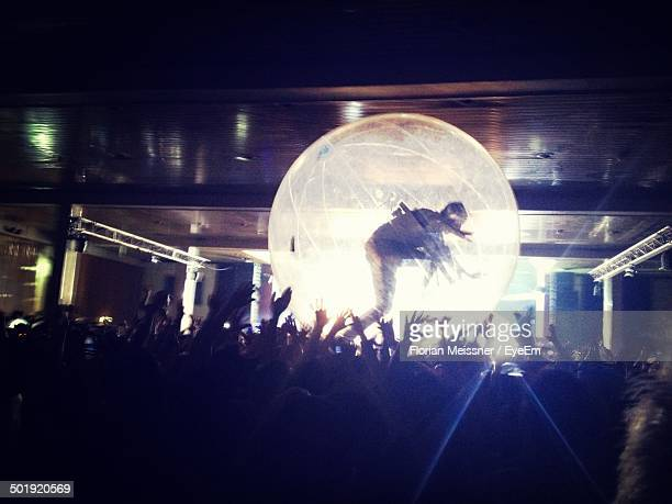 Woman in transparent ball along people at an event