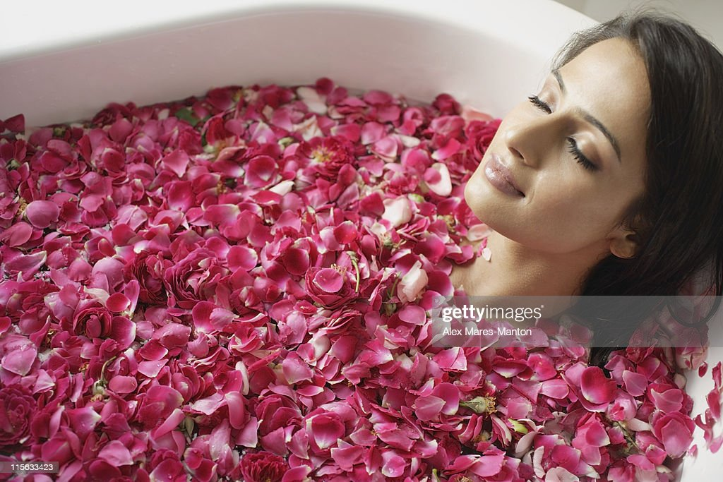 woman in tub with floating petals : Stock Photo