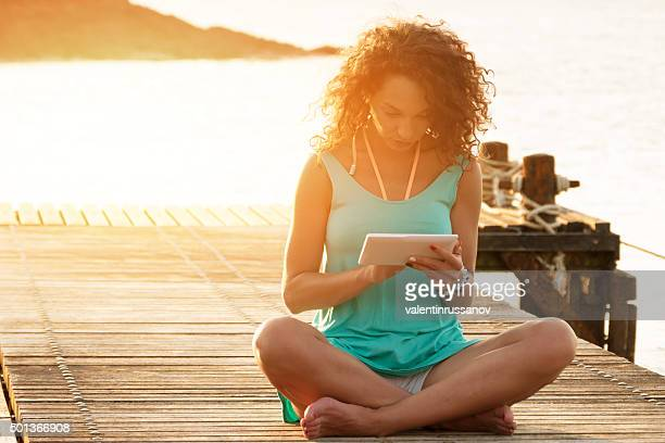 Femme en robe turquoise assis sur la jetée