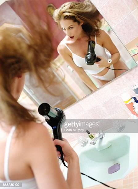 Woman in underwear, drying hair in front of bathroom mirror