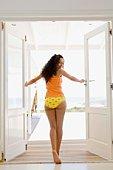 Woman in underwear opening door to veranda