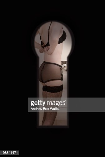 woman in underwear undressing, through keyhole : Stock Photo