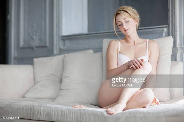 Woman in underwear watching her legs on a sofa