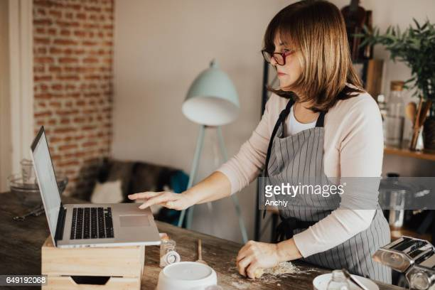 Woman in using laptop from domestic kitchen