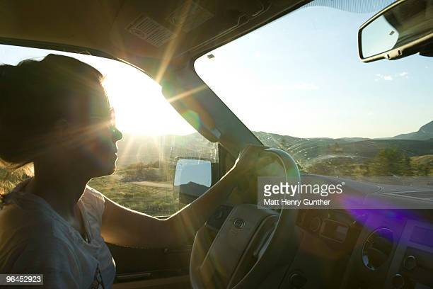 Woman in vehicle with light shining through window