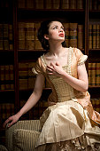 Woman in Victorian dress in a library