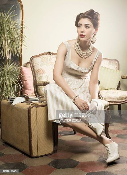 Woman in vintage clothes waiting in lobby with suitcase