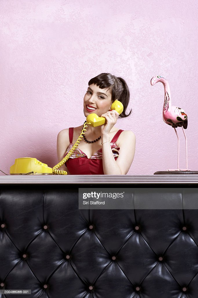 Woman in vintage dress using rotary phone on counter : Stock Photo