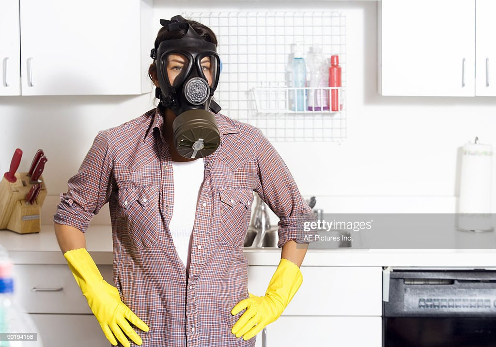 Woman in vintage gas mask cleaning : Stock Photo